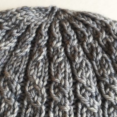 a detail of top of Stormy Harbour Hat by Imagined Landscapes Designs, Sweet Georgia Yarn
